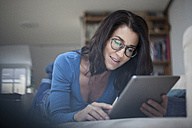 Woman at home using digital tablet - RBF003658
