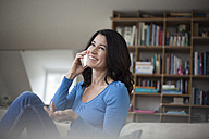 Smiling woman at home on cell phone - RBF003661