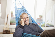 Smiling mature man at home on cell phone lying in hammock - RBF003679