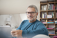 Portrait of mature man at home holding digital tablet - RBF003691