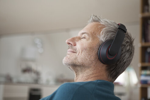 Relaxed man at home wearing headphones listening to music - RBF003694