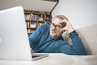 Mature man at home lying on couch using laptop - RBF003700