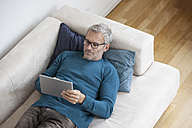 Mature man at home lying on couch using digital tablet - RBF003706