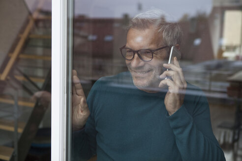 Smiling man behind windowpane on cell phone - RBF003709