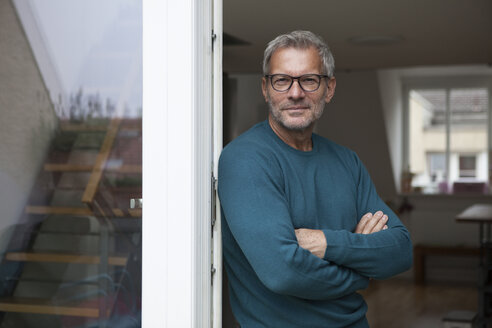 Portrait of mature man leaning against balcony door - RBF003712