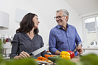 Mature couple with digital tablet cooking in kitchen - RBF003727