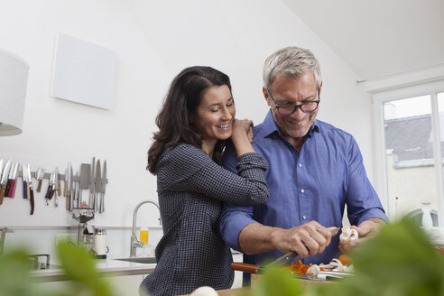 Mature couple preparing vegetables in kitchen - RBF003730