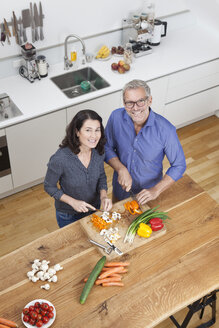 Mature couple preparing vegetables in kitchen - RBF003733