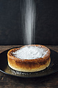 Sprinkling Japanese cheese cake with icing sugar - IPF000279