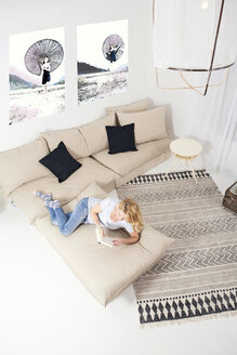 Blond woman lying on the couch at home reading a book - MAEF011158