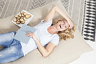 Portrait of laughing blond woman lying on the couch with a book and plate of cookies - MAEF011161