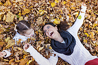 Happy girl with mother lying in autumn leaves - HAPF000066
