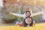 Happy family lying in autumn leaves - HAPF000069