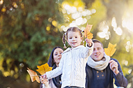 Smiling girl with family holding autumn leaf - HAPF000075