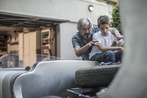 Grandfather and grandson restoring a car together - ZEF007631