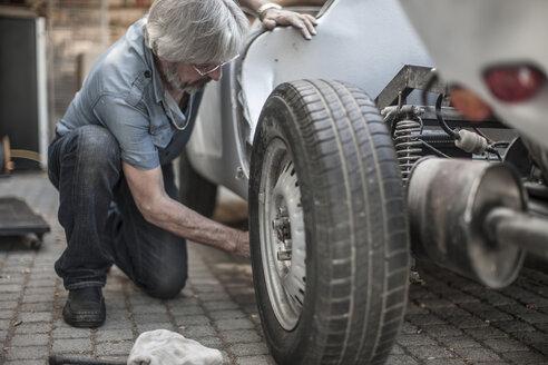 Senior man restoring a car - ZEF007634