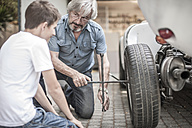 Grandfather and grandson changing car tire - ZEF007637