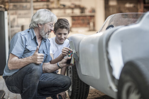 Grandfather and grandson restoring a car together - ZEF007640