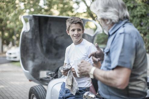 Grandfather and grandson restoring a car together - ZEF007646
