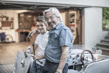 Portrait of grandfather and grandson restoring a car together - ZEF007649