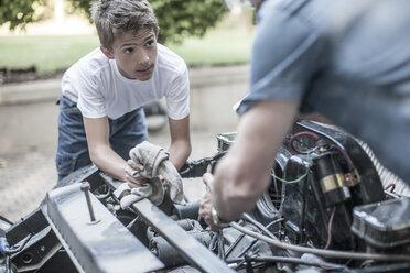 Grandfather and grandson restoring a car together - ZEF007652