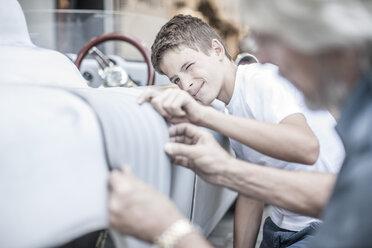 Boy with grandfather scrutinizing car - ZEF007655
