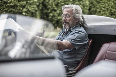 Senior man in sports car looking at check list drinking lemonade - ZEF007661