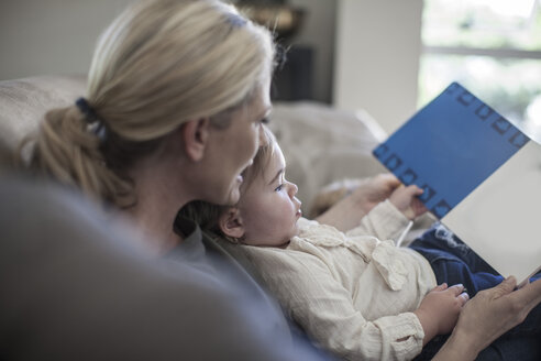 Mother and baby girl at home looking at book - ZEF007664