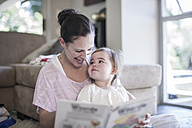 Mother and baby girl at home looking at book - ZEF007673