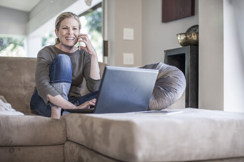 Woman sitting on couch with cell phone and laptop - ZEF007682