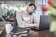 Man sitting at dining room table working at home - ZEF007697