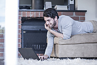 Man lying on couch looking at laptop - ZEF007700