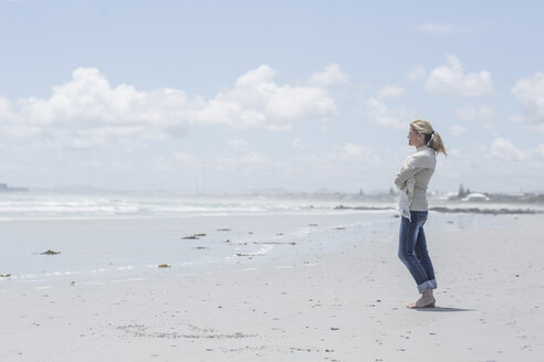 Woman standing on the beach looking at distance - ZEF007715