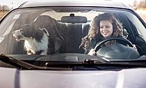 Woman driving car, dog sitting on passenger seat - OIPF000038