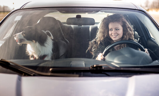 Woman driving car, dog sitting on passenger seat - OIPF000038