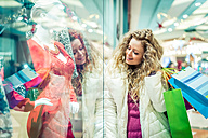 Italy, Lombardy, Milan, Woman with shopping bags in a shopping center - OIPF000050