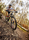 Mountain biker driving in the forest - MGOF001203