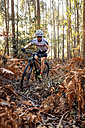 Mountain biker driving in the forest - MGOF001206