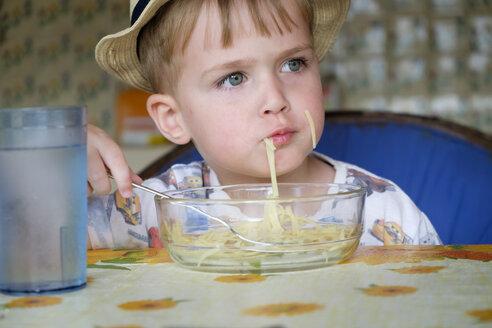 Portrait of little boy eating spaghetti - ABAF001965