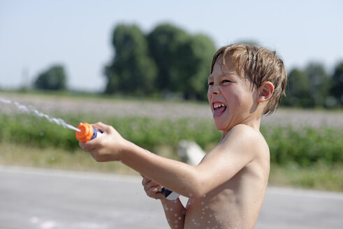 Boy splashing with water gun in summer - LBF001323