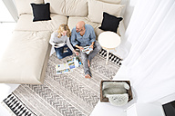 Couple sitting on the floor of their living room looking at travel catalogues - MAEF011169