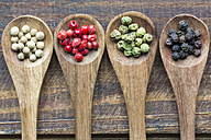 Row of four wooden spoons of different peppercorns - SARF002408