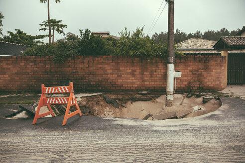 Brazil, Florianopolis, traffic barrier on broken tarmac after heavy rainfalls - MFF002567