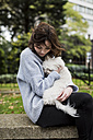 Young woman cuddling with her dog - MAUF000186