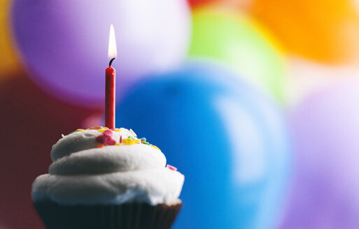 Birthday cup cake with lighted candle in front of balloons - SELF000083
