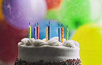 Blown out birthday candles on a cake in front of balloons - SELF000089