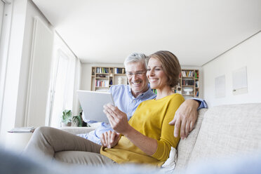 Smiling couple sitting on the couch at home using digital tablet - RBF003748