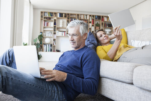 Couple relaxing in the living room with digital devices - RBF003754