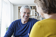 Smiling man communicating with his wife at home - RBF003757