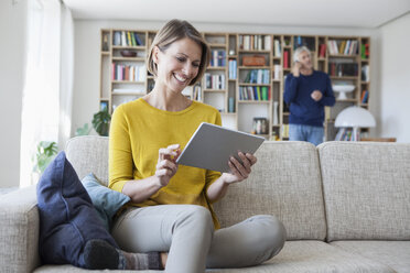 Smiling woman sitting on the couch  using digital tablet while her husband telephoning in the background - RBF003763